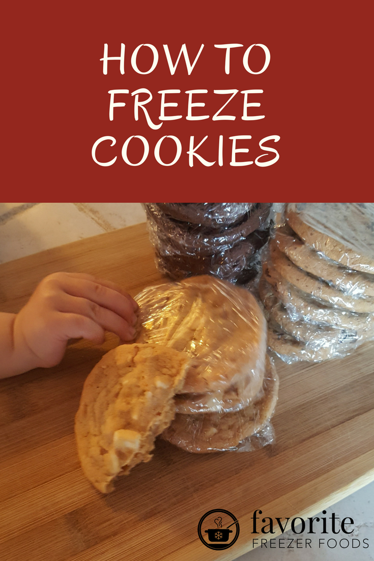 Toddler reaches for a single cookie from a stack of baked cookies wrapped for the freezer. Text overlay states